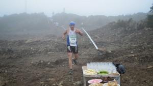 Un corredor entre la niebla se acerca al avituallamiento