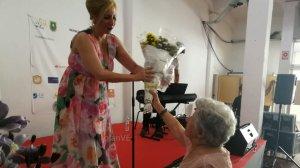 La señora María Magdalena entrega un ramo a Pilar Boyero en agradecimiento