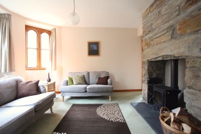 Lodge living room with stone fireplace, wood-burner, arched windows and TV/DVD