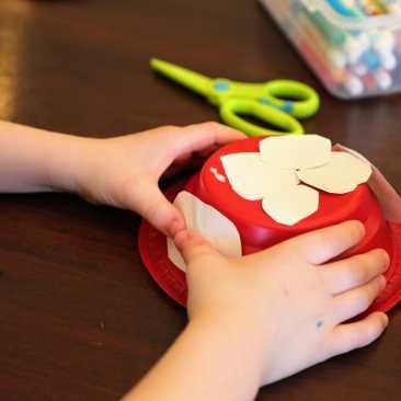 Child taping white circles onto mushroom house