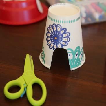 Child cutting paper cup