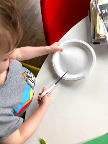Child cutting paper plate for peas in a pod craft