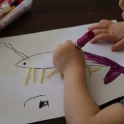 Child coloring a shrimp