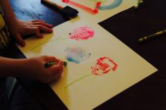 Child coloring stems of bok choy roses