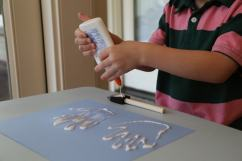 Child putting glue on brush