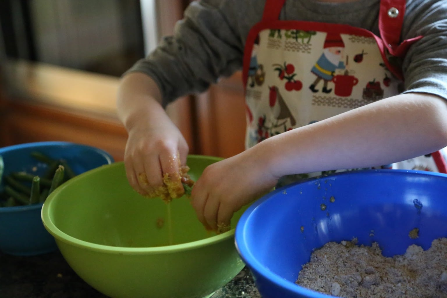 Child dipping green bean into bowl of whisked eggs