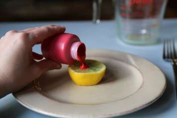 chid pouring red paint on lemon volcano