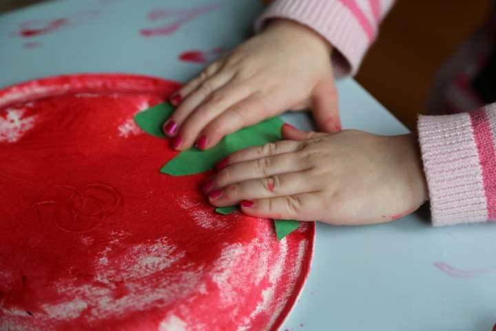 Child pasting stem onto red tomato plate