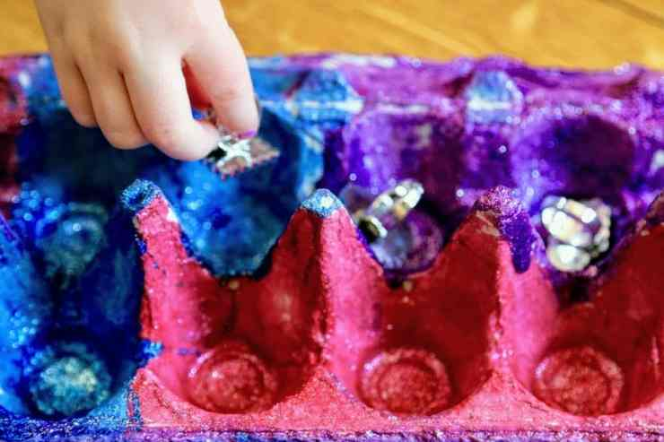 child placing treasures in egg carton