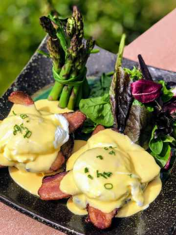 Bacon and Eggs Benedict with Mixed Greens & Asparagus on plate