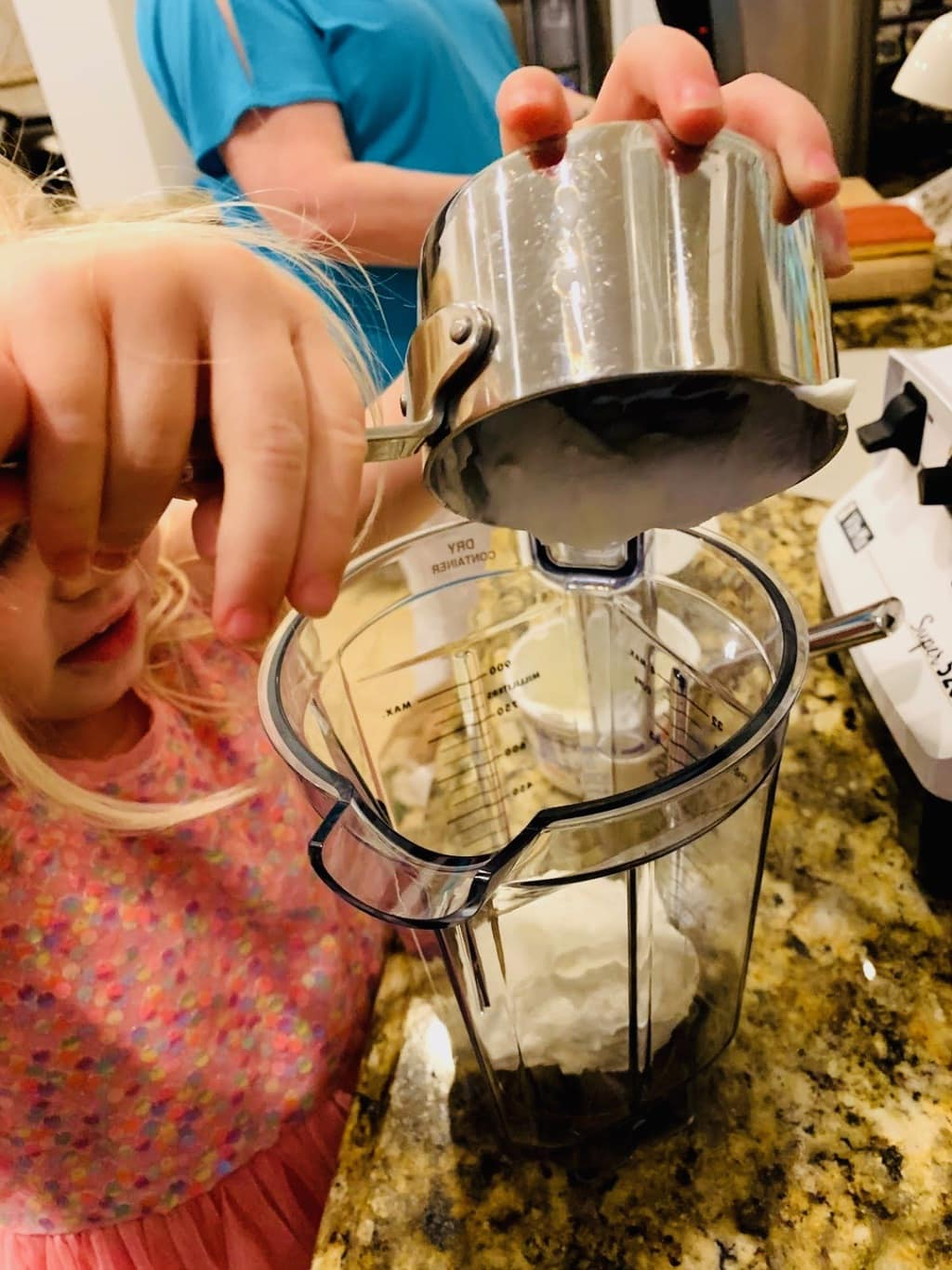 child adding sour cream to vitamix