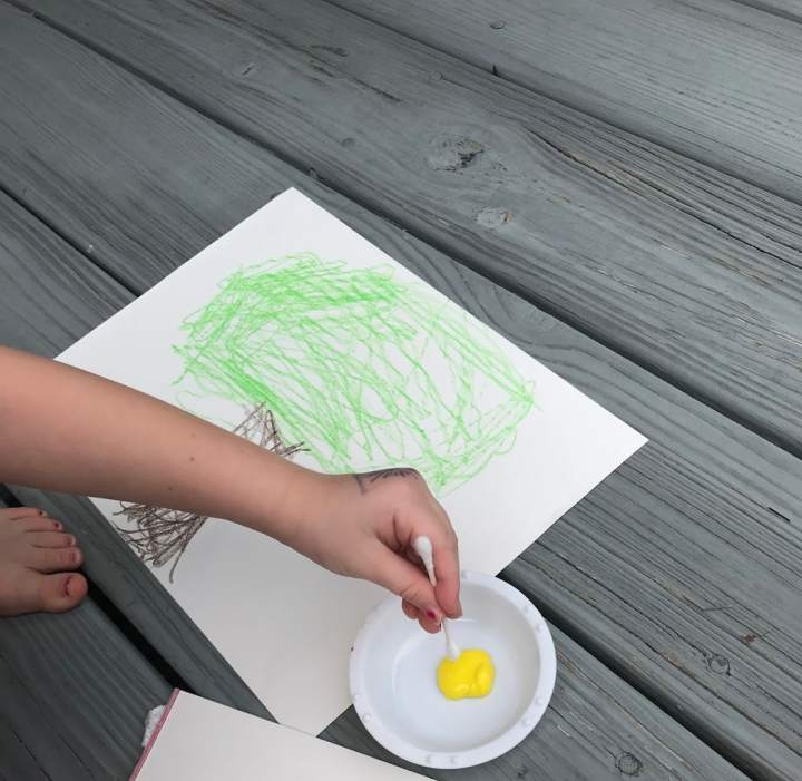 child dipping qtip into yellow paint