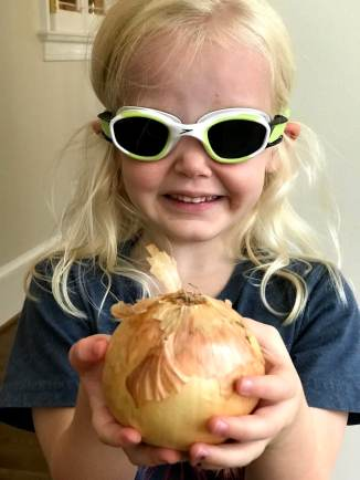Child weating goggles to cut onion