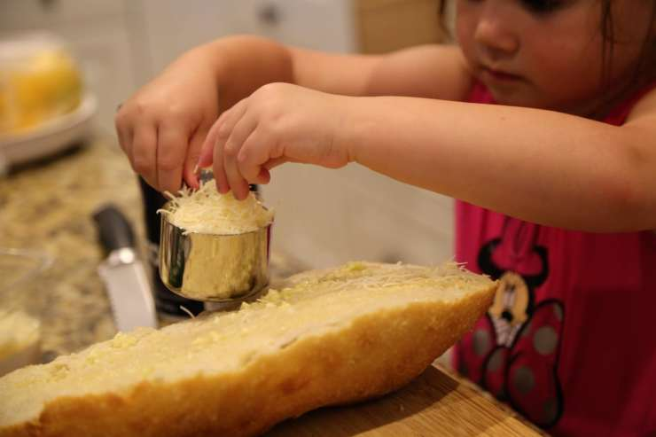 child adding cheese to bread