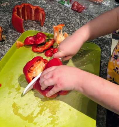 Child cutting red bell pepper 2