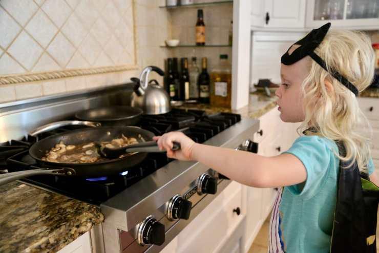 child stirring classic beef stroganoff sauce