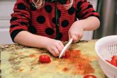 child chopping tomato