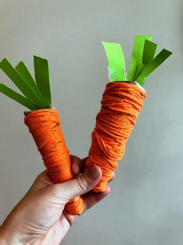 hand holding two play food carrots