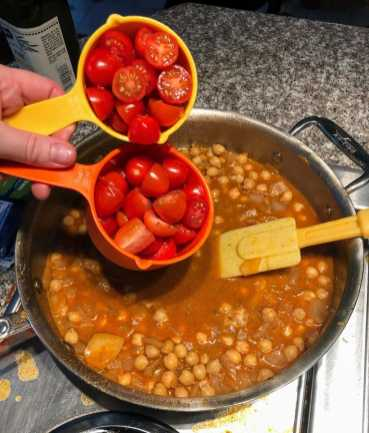 Pouring tomatoes into chickpea sauce
