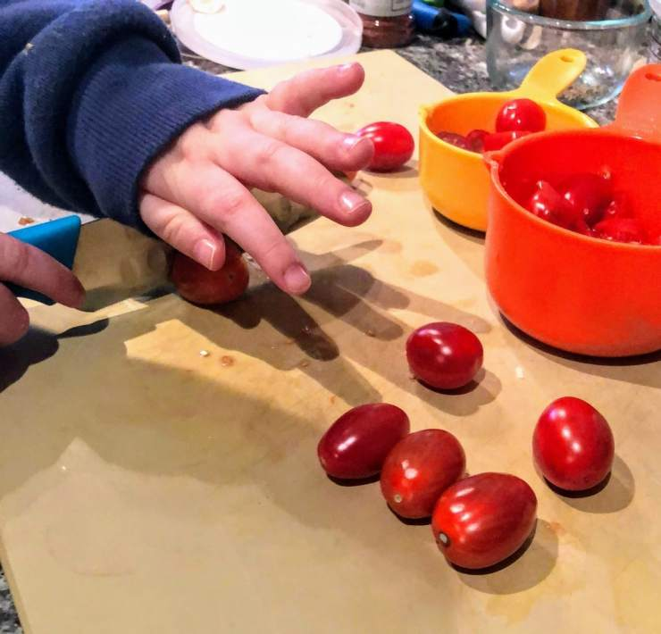 child cutting grape tomatoes on a large cutting board, with a kids kitchen knife