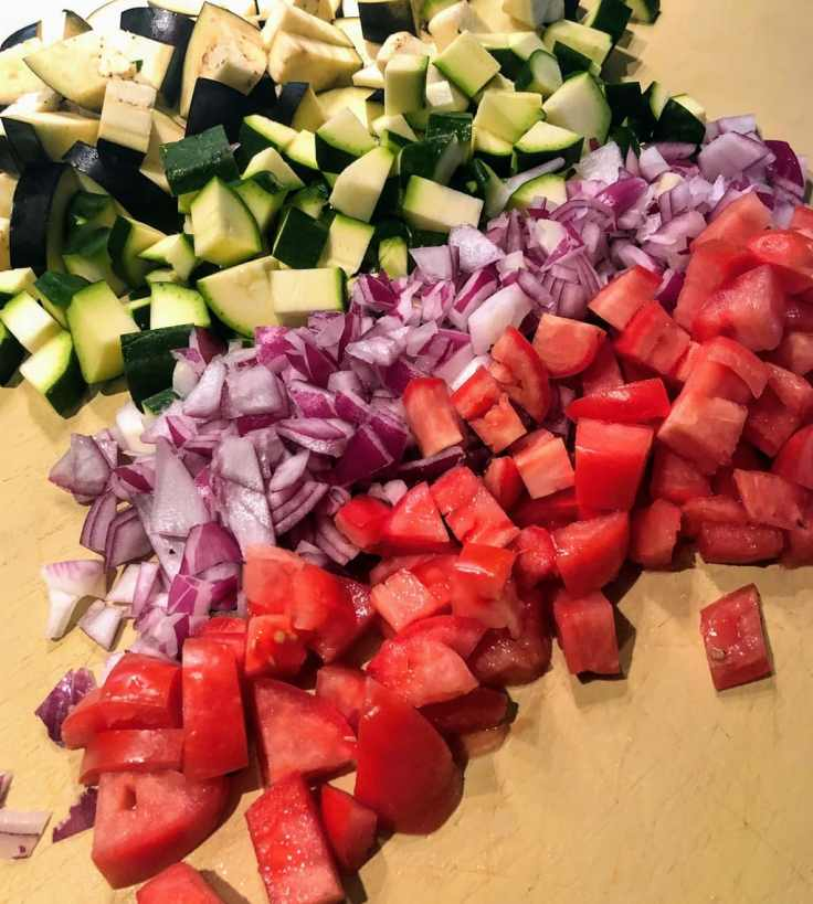 chopped zucchini, red onion and tomato on cutting board
