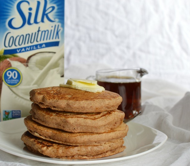 stack of four pancakes on white plate next to syrup and coconut milk carton