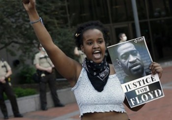 A girl holds up a sign saying justice for floyd with his face on it