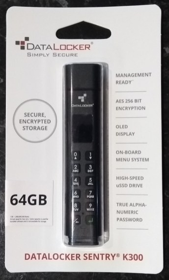 "Datalocker sentry k300 in packaging, from the front. Features declared are ""secure, encrypted storage"", ""management ready"", ""aes 256 bit encryption"", ""oled display"", ""on-board menu system"", ""high-speed uSSD drive"" and ""true alpha-numeric password""."