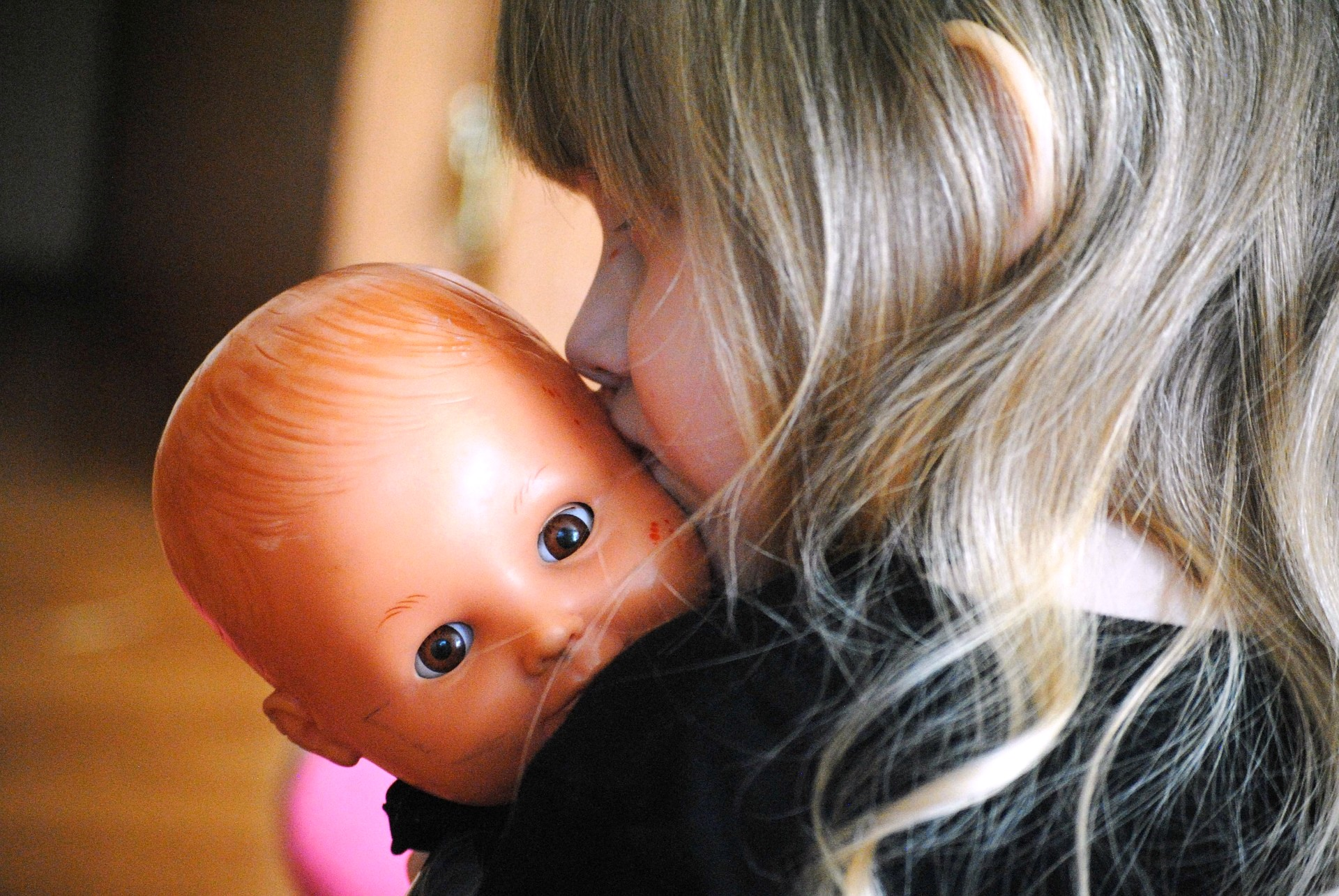 Child comforting baby doll
