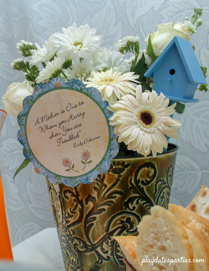 """White flowers in a green vase with blue accents, and a card with the quote """"A Mother is One to whom you hurry when you are troubled"""" by Emily Dickenson"""