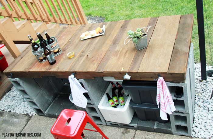 Using a pallet, cinder blocks, some extra wood, and corrugated steel roofing, you can create a stunning outdoor bar like this!