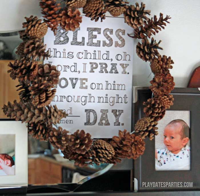 This pine cone wreath surrounds a custom print at a brown and white, fall inspired baptism for a baby boy.