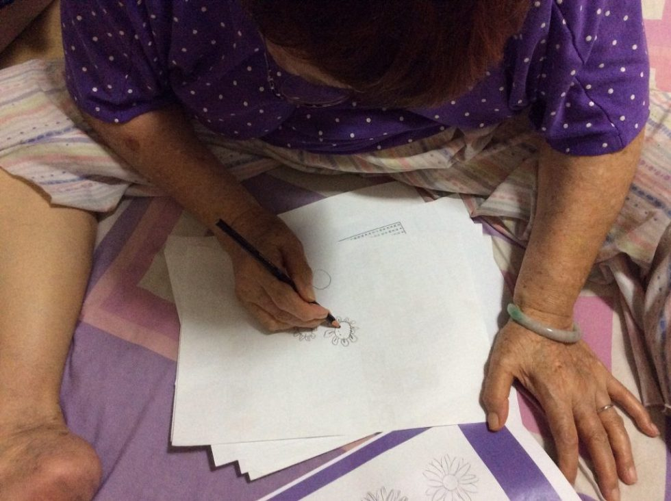 My grandma following the Step by Step Sketch guide to draw the petals of a flower.