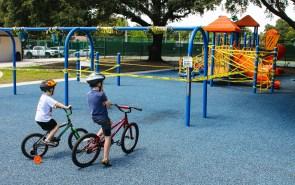 Children staring at closed playground equipment