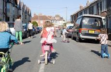 children cycling and scooting in road