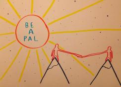 "A drawing of two mountains and on top of each mountain is a simple human-like figure, they have long arms stretching across the gap between the mountains to hold each other's hand. There is a large sun in the corner of the drawing which has the words ""Be a Pal"" written inside it."