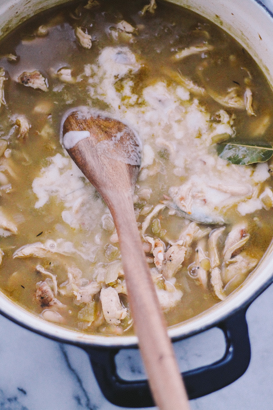 white chili via playswellwithbutter | packed with flavor from a carefully built base of onions, chili peppers, & warm spices, this white chili is braised with beer, loaded with pulled roasted chicken breast, & thickened with masa harina. oh, & if that didn't win you over, spoonfuls of white chili make for the perfect vessel for guacamole. #boom.