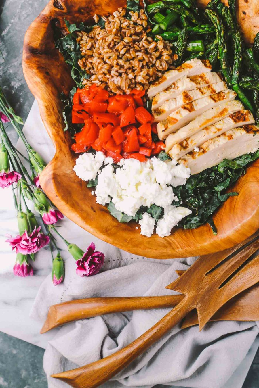 this kale salad will keep you coming back for more! perfect for a simple weeknight al fresco girls' night with a bottle rosé, or meal prep for a week's worth of delicious, healthy lunches at the office! kale & asparagus are paired with lemon thyme chicken, nutty farro, tangy goat cheese, & roasted red pepper. tossed in a lemon thyme vinaigrette. | salad recipe, homemade dressing, meal prep, girls night idea, spring recipe, summer recipe, healthy recipe |