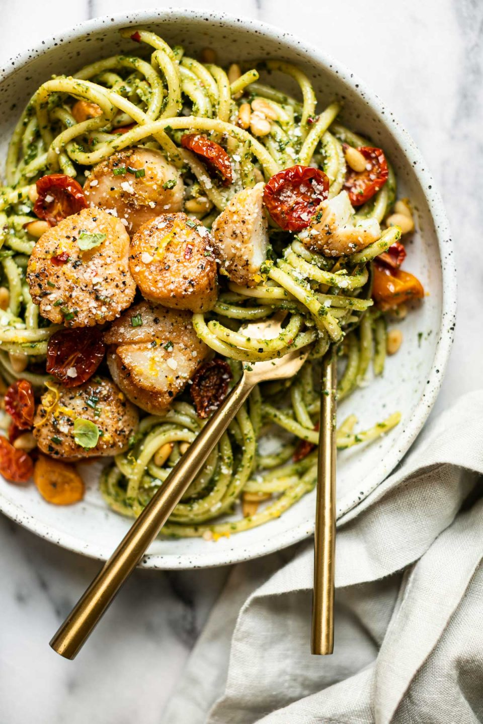 Seared Scallops and Kale Pesto pasta in a black & white speckled pasta bowl. A gold fork & spoon rests inside the bowl & is tucked into the pasta ready to serve. The bowl sits on a grey and white marble surface. A light grey linen napkin is tucked under the platter in the foreground.