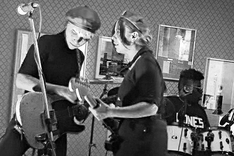 Lead guitarist Carmen Vandenberg, lead singer and rhythm guitarist Rosie Bones, Drummer Heavy performing at Ludlow House.