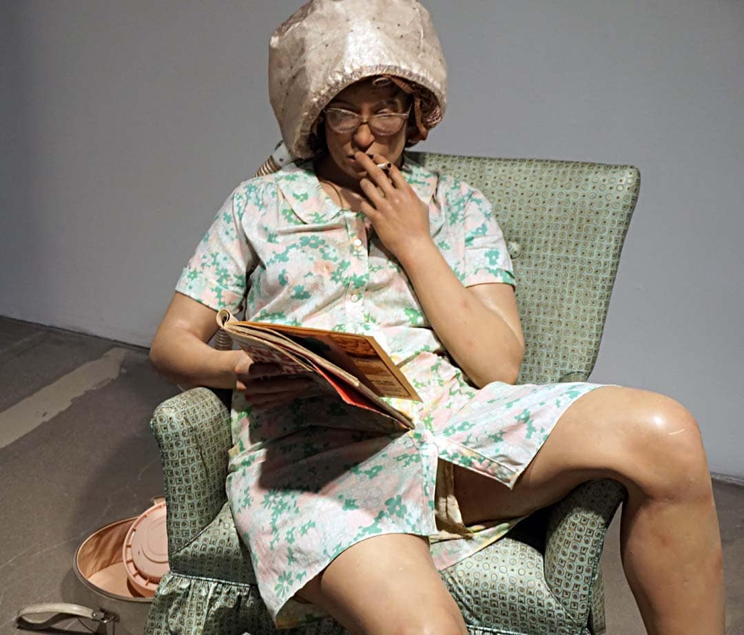 "Duane Hanson, American, 1925-1996 ""Housewife, 1969-1970: polyester, resin, and fiberglass, polychromed in oil and mixed media, with accessories"" ""Hanson's typically lower and middle-class characters are empathetically portrayed in private or mundane moments; their appearance is at once startlingly present yet distinctly at odds in a gallery setting, where they are encountered almost voyeuristically, thus amplifying their isolation."""