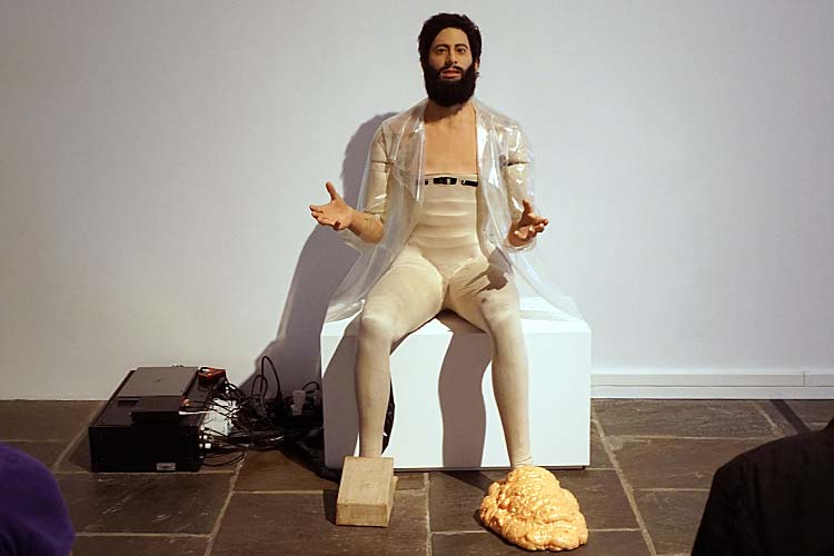 """To the Son of Man Who Ate the Scroll, 2016. Android, plastic coat, expandable foam shoe, and cardboard and linen shoe."" - Goshka Macuga, Polish, born 1967 ""Part human, part robot, the android is a consummate figure for reflection on the boundaries between man and machine. He recites a monologue comprising spliced excerpts from notable writings and speeches; from Thomas Paine and Albert Einstein to Ayn Rand and Martin Luther King Jr."""