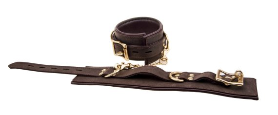 A pair of Bound Nubuck Leather wristcuffs with one cuff closed and the other open and laying flat