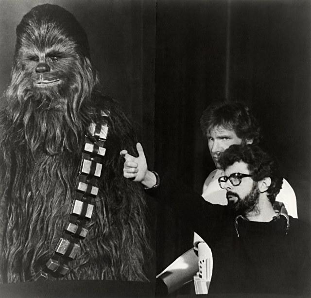 Peter Mayhew (1944-2019) como Chewbacca, Harrison Ford como Han Solo y el director George Lucas en el set de  Star Wars (1977). Imagen: StarWars.com