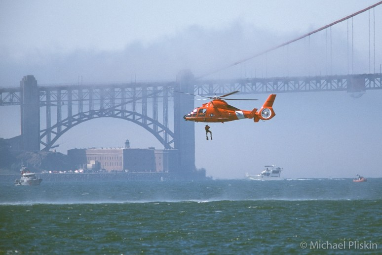 U.S. Coast Guard HH-65 Dolphin helicopter demonstrates a water rescue near the Golden Gate Bridge in San Francisco.