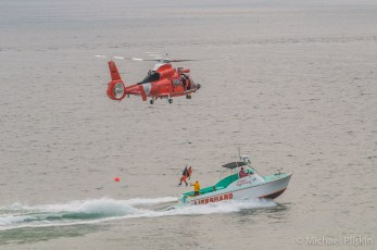 HH-65 Dolphin, USCG Helicopter, lifts rescue victim from speeding Lifeguard boat.