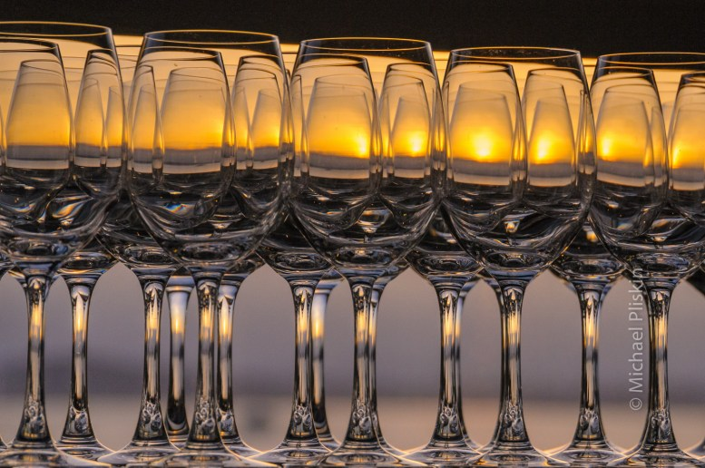 Sunset over Puget Sound in Seattle, WA, as seen through an array of wine glasses