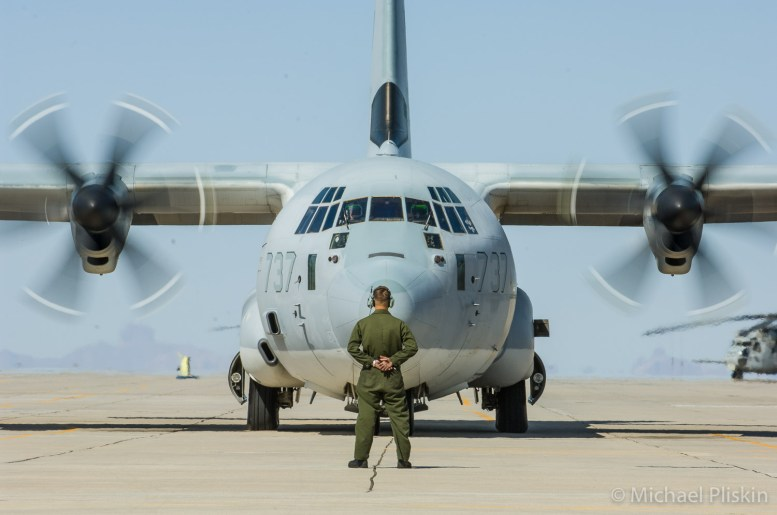 Ground crewman halts progress of C-130 Hercules
