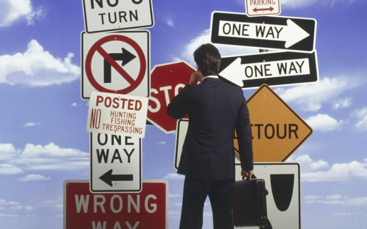 man looking at confusing signs