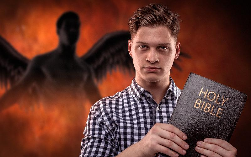man holding Bible with fallen angel behind him